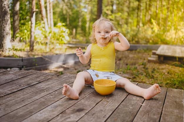 Piccolo e simpatico bambino biondo carino con vestiti sporchi e faccia che mangia frutta o