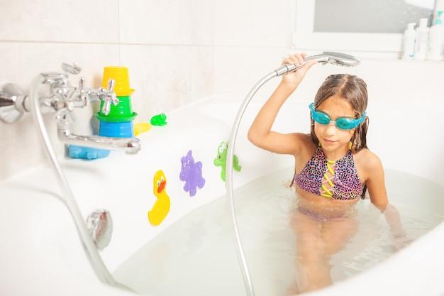 Piccola ragazza divertente in occhiali da bagno blu guarda la telecamera e sorride in modo affascinante mentre si versa l'acqua della doccia su se stessa
