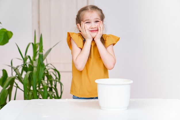 La piccola ragazza divertente tiene le mani nella farina sulle guance. hobby culinario dei bambini. ricetta semplice e deliziosa. scuola di cucina.