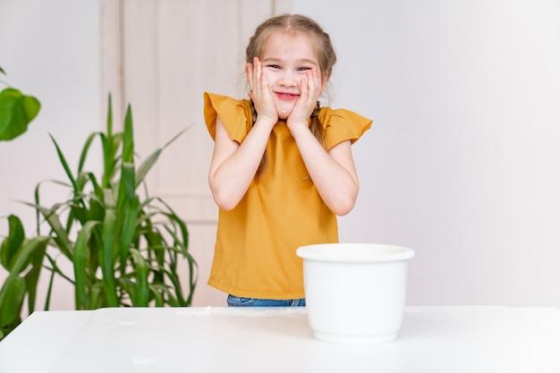 La piccola ragazza divertente tiene le mani nella farina sulle guance. hobby culinario dei bambini.