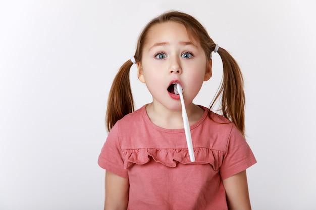 La piccola ragazza divertente ha aperto la bocca con uno spazzolino da denti