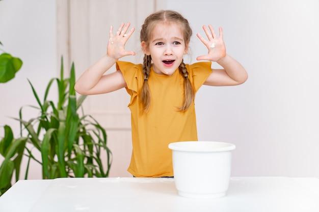 Una bambina divertente mostra le mani spalmate di farina