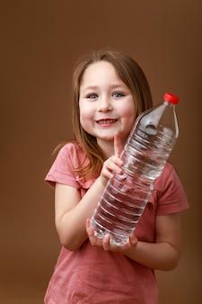 Piccola ragazza divertente con una bottiglia d'acqua