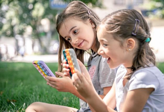 Piccole ragazze divertenti all'aperto con telefoni in una custodia con brufoli pop, un giocattolo antistress alla moda.