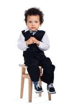 Piccolo signore. piccolo neonato africano che guarda l'obbiettivo mentre è seduto su uno sgabello su sfondo bianco