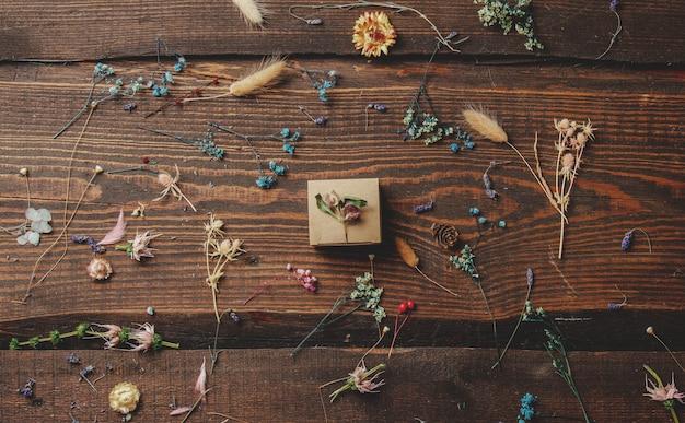 Piccola confezione regalo accanto a erbe secche sul tavolo di legno