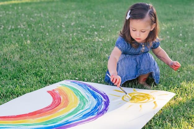 La bambina di 2-4 anni dipinge arcobaleno e sole su un grande foglio di carta, seduta su un prato verde