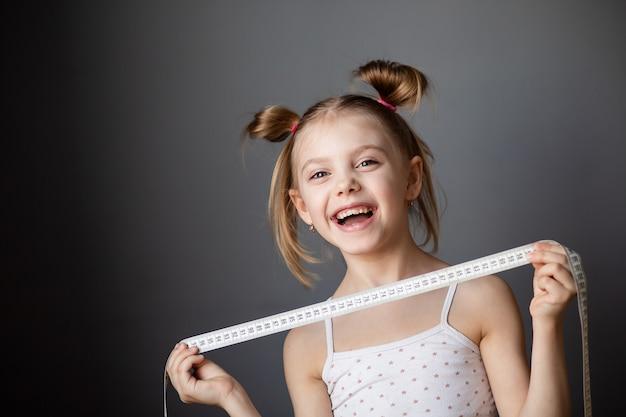 Bambina 7-8 anni che ride, bambino con un metro a nastro (centimetro) su una parete grigia