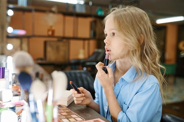 La bambina applica la pomata allo specchio nel salone di trucco