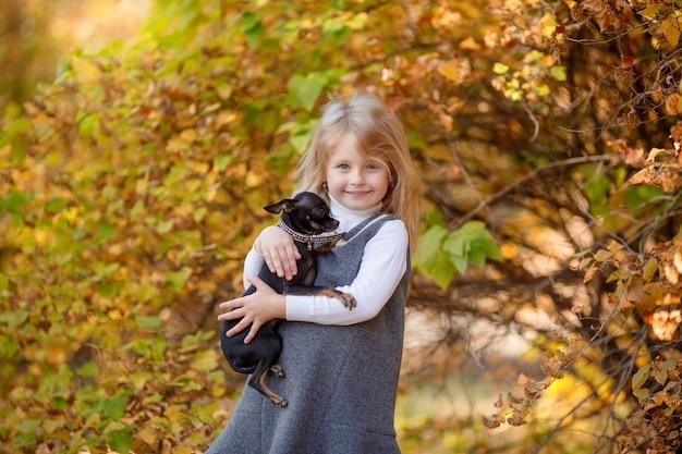 Bambina in autunno nel parco che tiene un piccolo cane sorride