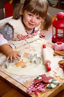 Bambina che cuoce i biscotti di natale che tagliano pasticceria con un cooki
