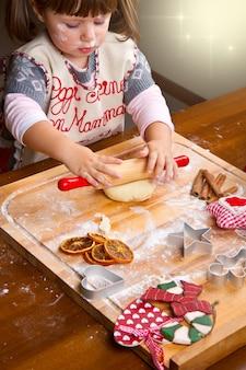 Bambina che cuoce i biscotti di natale che tagliano la pasticceria con una taglierina del biscotto