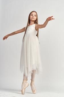 Piccola ballerina della ragazza in un vestito bianco in scarpe da punta