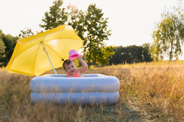 La bambina bagna in uno stagno gonfiabile.