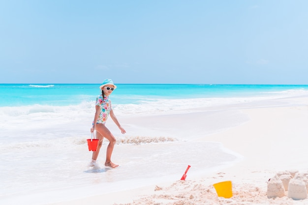 La bambina sulla spiaggia gioca con la sabbia e fa il castello di sabbia