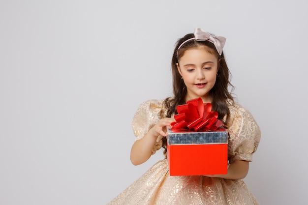 Una bambina in un bel vestito tiene una confezione regalo su uno sfondo bianco