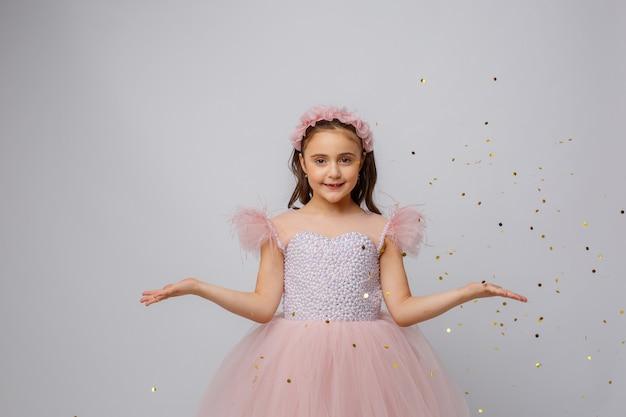 Bambina in un bellissimo vestito prinses su uno sfondo bianco