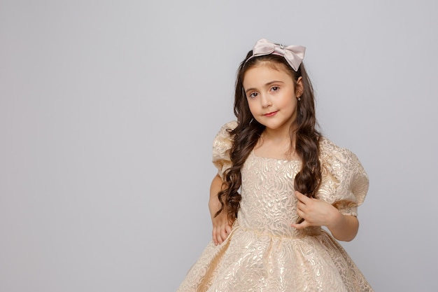 Bambina in un bel vestito su uno sfondo bianco