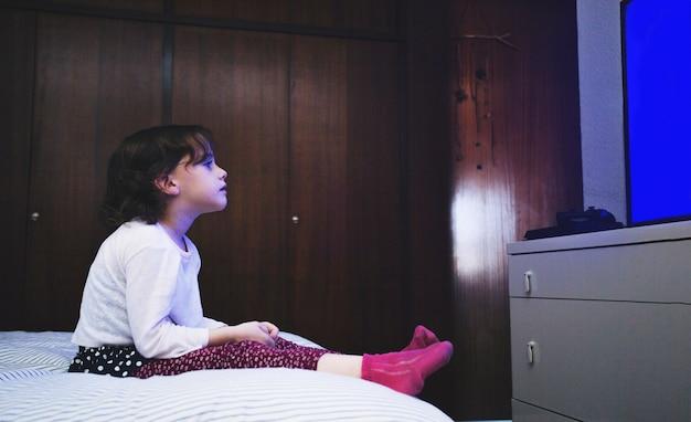 Bambina sul letto a guardare la tv