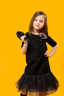 Bambina in abito nero con microfono