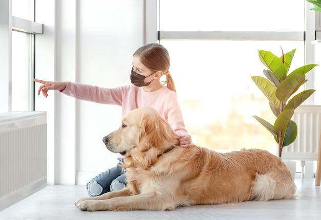 Bambina in maschera nera che si siede con il cane golden retriever sul pavimento e mostrandogli qualcosa per strada