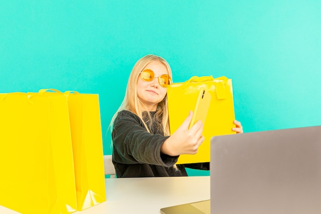 La bambina blogger fa rivedere online qualcosa con registrato utilizzando lo smartphone su sfondo azzurro.
