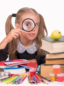 La bambina bionda in un vestito scolastico guarda attraverso una lente d'ingrandimento su uno sfondo bianco