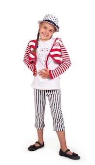 Bambina, bionda in un vestito estivo alla moda in posa in studio su uno sfondo bianco. in un cappello e pantaloni a righe alla moda. concetto di acquisto.