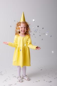 La bionda della bambina in un vestito giallo cattura sorridere dei coriandoli felice su spazio bianco