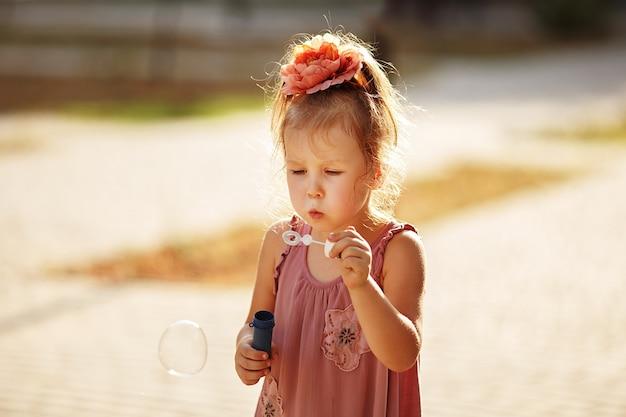 Bambina che soffia bolle di sapone nella sosta di autunno
