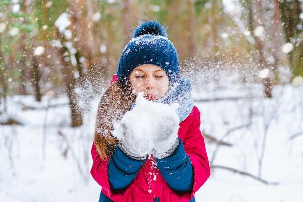 La bambina soffia la neve con guanti su uno sfondo bokeh di fiocchi di neve nella foresta di inverno