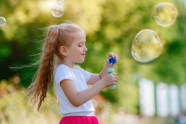 La bambina soffia bolle di sapone nel parco in estate