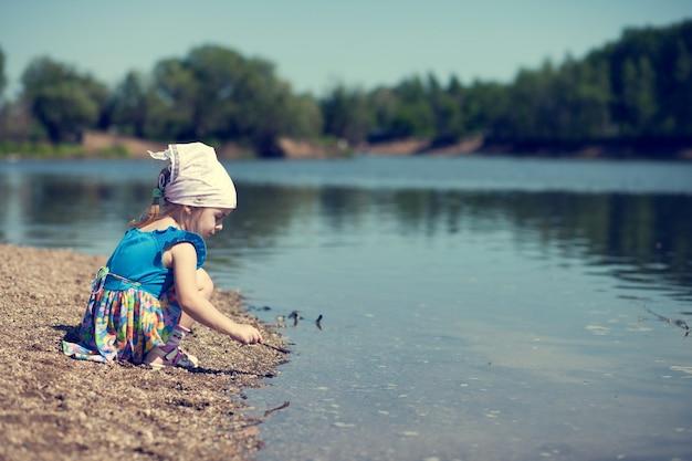 Bambina in vestito blu che gioca al lago