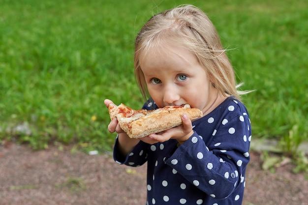 Bambina in un vestito blu con pois bianchi che mangia una grande fetta di pizza su uno sfondo di erba verde