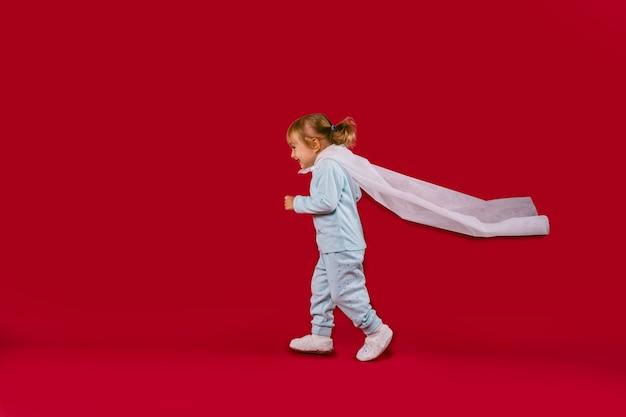 Una bambina in pigiama blu, pantofole bianche e un mantello bianco di un eroe fatto a mano corre e il mantello viene aperto. .