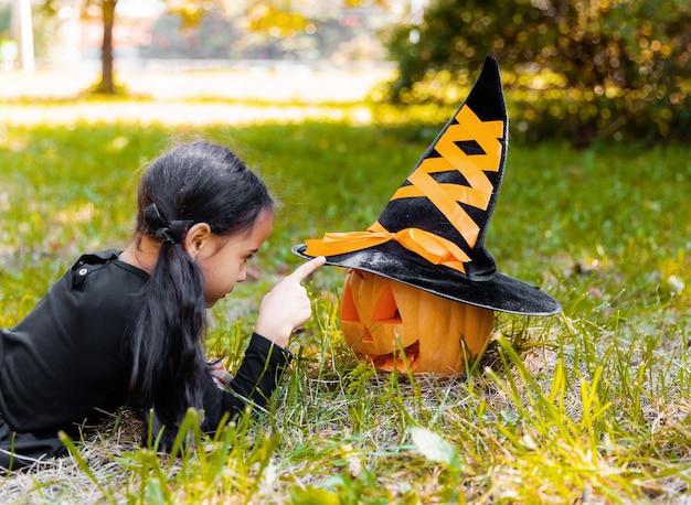 Bambina e ragazzo che intagliano la zucca di halloween. bambini travestiti dolcetto o scherzetto. bambini dolcetto o scherzetto. bambino in costume da strega che gioca nel parco autunnale. bambino con jack-o-lantern.