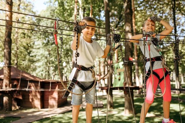 Bambina e ragazzo si arrampica nel parco avventura. bambini che si arrampicano sul ponte sospeso