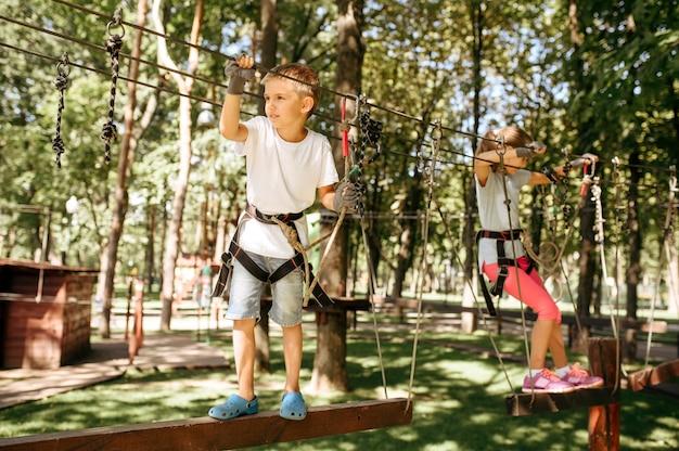 Bambina e ragazzo si arrampica nel parco avventura