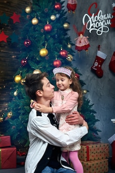 Una bambina e un ragazzo che abbraccia vicino all'albero di natale a capodanno e natale. sullo sfondo le lettere russe parole: felice anno nuovo.