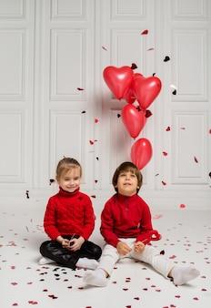 Una bambina e un ragazzo si siedono sul pavimento e catturano coriandoli rossi su sfondo bianco con palloncini rossi