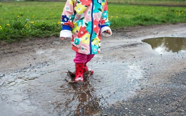 Una bambina con una giacca luminosa e stivali rossi salta allegramente tra le pozzanghere. atmosfera primaverile.