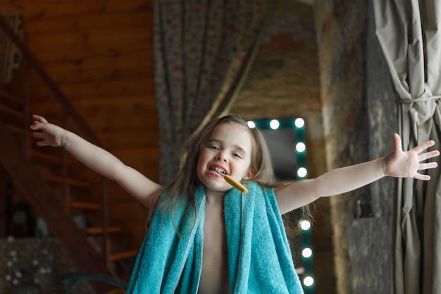 Una bambina si lava i denti in bagno. ritratto di un bambino con uno spazzolino da denti