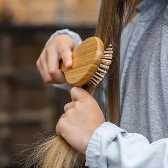 Bambina che spazzola i suoi capelli