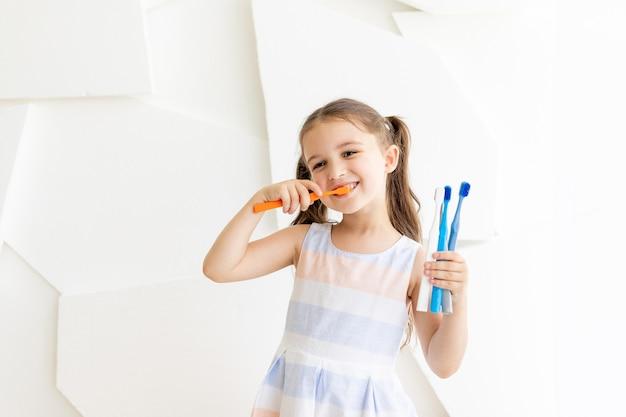 Bambina lavarsi i denti e tenendo gli spazzolini da denti