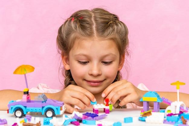 Una bambina costruisce una casa con un kit di costruzioni colorato.
