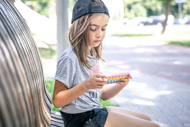 Una bambina con un berretto usa uno smartphone seduto su una panchina nel parco in una giornata estiva.