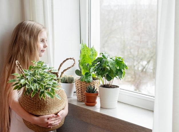 Bambina che si prende cura di piante da appartamento a casa