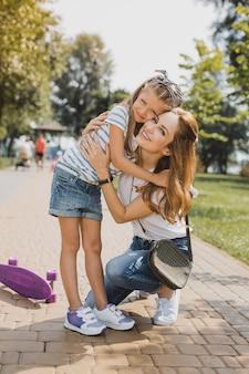 Piccola ragazza. giovane bella madre premurosa che abbraccia la sua bambina che indossa pantaloncini jeans alla moda