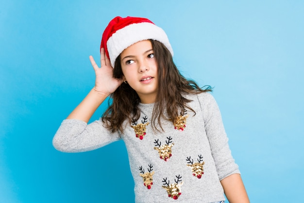 Bambina che celebra il giorno di natale che prova ad ascoltare un gossip.