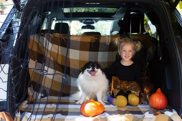 Bambina che celebra il divertimento del bagagliaio dell'auto del cane di halloween all'aperto